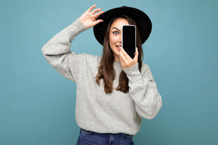 Pretty young smiling woman wearing black hat and grey sweater holding phone looking at camera isolated on background