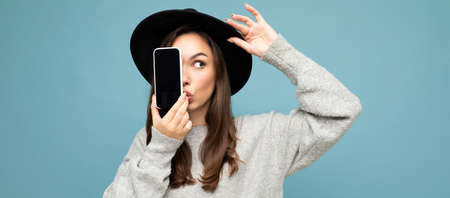 panoramic Photo of Beautiful amazed positive woman wearing black hat and grey sweater holding mobilephone showing smartphone isolated on background looking to the side Banco de Imagens