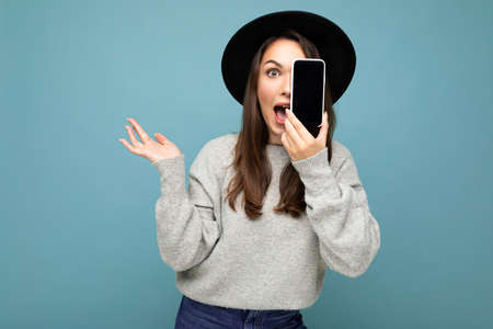 positive lady student wearing black hat and grey sweater holding mobilephone showing smartphone isolated on background looking at camera with hand