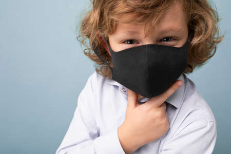 Closeup photo of handsome curly blonde little boy in medical black mask standing isolated over blue background. Coronavirus concept