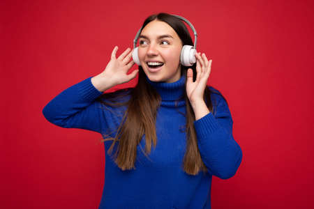 Photo of beautiful happy smiling young brunette woman wearing blue sweater isolated over red background wall wearing white wireless headphones listening to cool music and looking to the side