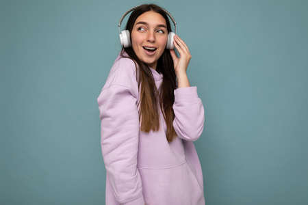 Beautiful happy smiling young brunette female person wearing light purple hoodie isolated over blue background wall wearing white wireless headsets listening to cool music and looking to the side