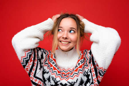 Young beautiful woman. Trendy woman in casual winter sweater. Positive female shows facial emotions. Funny model isolated on red background