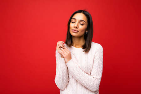 Attractive cute nice adorable tender young brunette woman in casual light knitted sweater isolated on red background with free space and enjoying