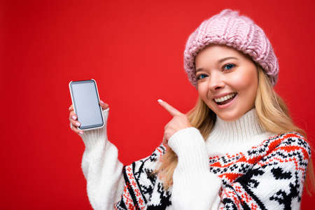 Photo of attractive smiling young blonde woman wearing warm knitted hat and winter warm sweater standing isolated over red background showing smartphone with empty screen for mock up looking at camera and pointing finger at gadjet.