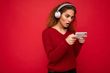 Pretty shocked young brunette curly woman wearing dark red sweater isolated on red backdrop wearing white headphones listening to music and using smartphone watching videos looking at gadjet display