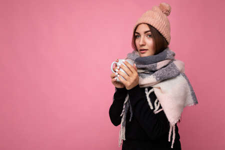 Beautiful young brunet woman wearing black sweater hat and warm scarf isolated over pink background holding paper mug for mockup drinking hot tea and looking at camera and having cold