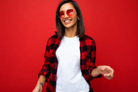 Portrait of positive cheerful smiling young brunette woman in casual white t-shirt for mockup, stylish red check shirt and trendy red sunglasses isolated on red background with copy space
