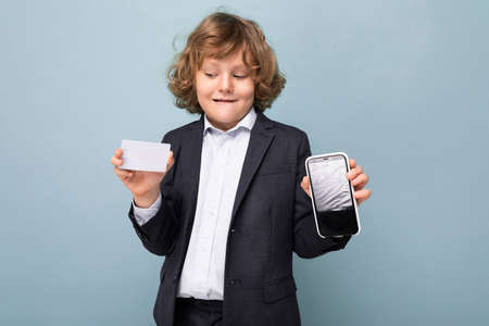 Handsome positive happy boy with curly hair wearing suit holding phone and credit card and showing mobile screen at camera isolated over blue background looking at plastic card