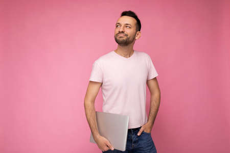Handsome happy young unshaven man holding laptop computer looking up in t-shirt on isolated pink background