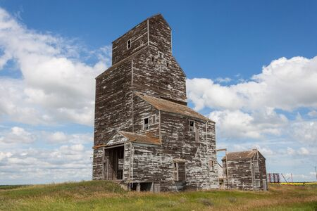 canada agriculture: Old Wooden Grain Elevator with Blue Sky and Clouds