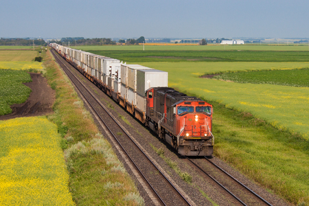 Container train on one of two tracks crossing colourful prairie Redactioneel