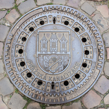 Manhole cover featuring Prague coat of arms Stock Photo