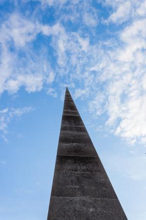 spire: Concrete Spire Reaching into a Blue Sky Stock Photo