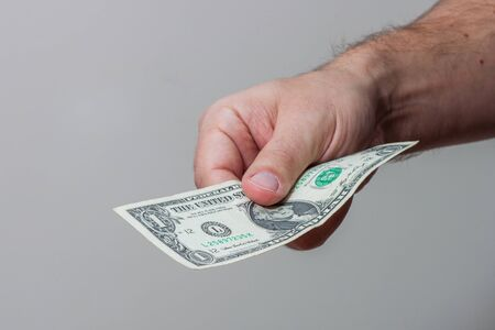 bank activities: Male hand giving  American one dollar bill
