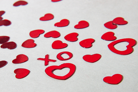 Red X and O in foreground and hearts scattered