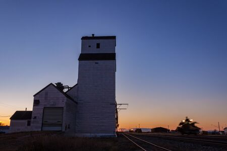 Wooden Grain Elevator at Sunset with Rail Machinery Moving Past