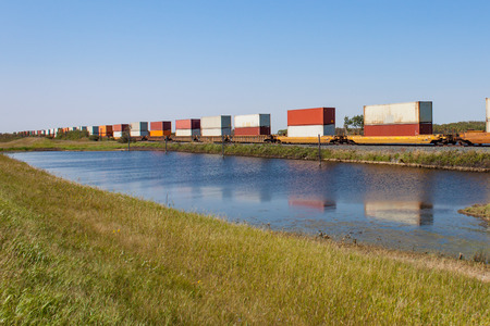 goods train: Reflections of Container Train in Pond in Summer