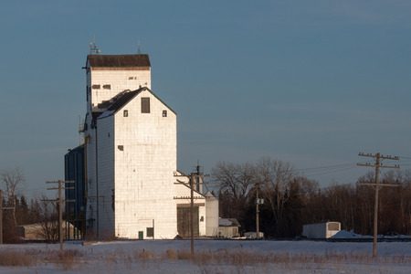 canada agriculture: White Grain Elevator at Sunset in Winter Stock Photo