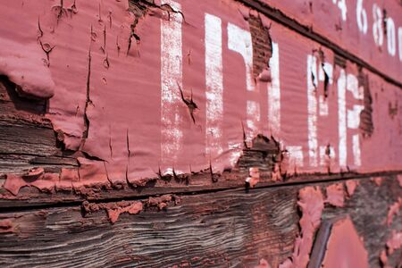 wood railways: Detail view of a freight railway car with the word IDLER and peeling red paint