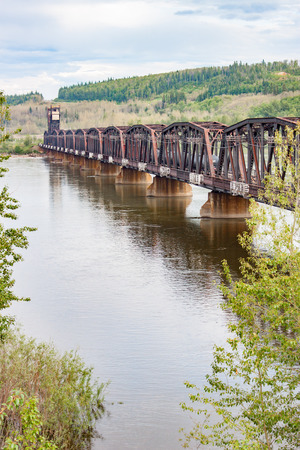 fraser river: A portrait view of a rusty railway bridge across the Fraser River in British Columbia
