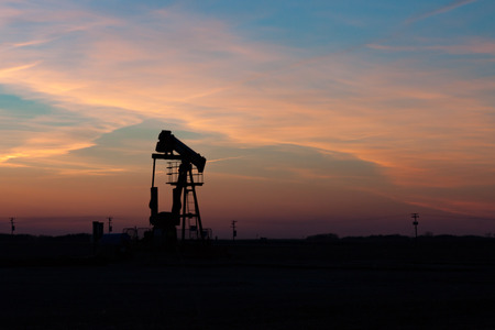 oil well: A single oil well pumpjack silhouetted against a prairie sunset