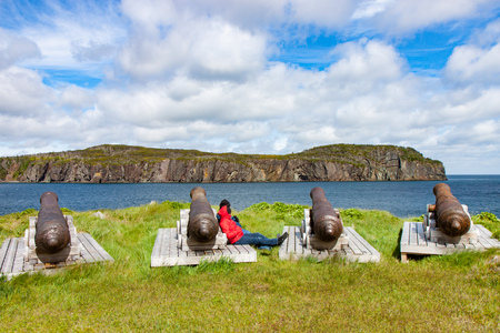newfoundland: A couple resting amongst a set of old cannons at Fort Point outside Trinity