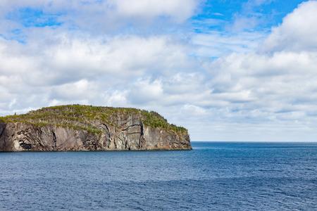 newfoundland: Rocky Peninsula thrusting into a Blue Ocean under Summer Sky