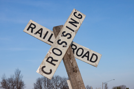 railroad crossing: White Railroad Crossing Sign Against Blue Sky Stock Photo