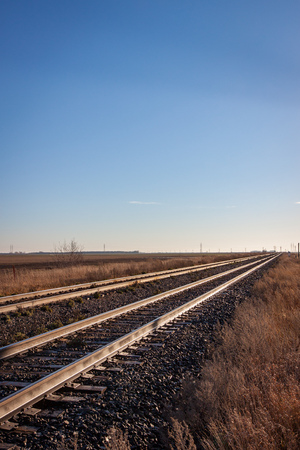 Two pairs of rails stretch to the prairie horizon