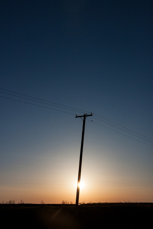 Silhouetted Power Pole On Canadian Prairie At Sunrise with Vertical Crop