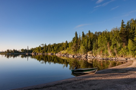 Sunrise on Kutimit Lake. A boat is grounded on a beach in a peaceful cove. Stock Photo