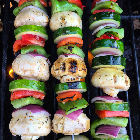 Three Colourful Shish Kabobs with Chicken Onions Mushrooms and Peppers on a Barbeque Фото со стока