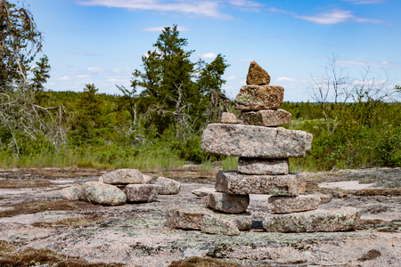 A large inukshuk stands on a broad rocky plain, part of the Canadian Shield