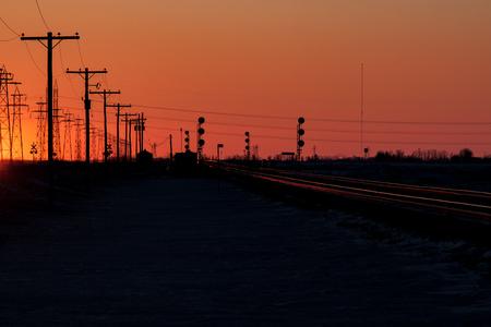 Telephone Poles and Railway Tracks in an Orange Sunset Stock Photo