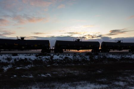 Black Railroad Tank Cars Silhouetted during Sunset 免版税图像