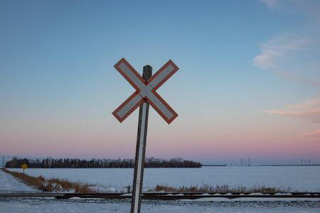 Traditional Railroad Crossing Sign at Sunset in Winter in Canada