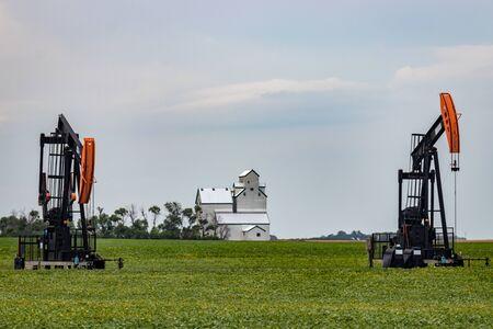 Pair of Oil Wells Flank Grain Elevator on Canadian Prairie Stock Photo