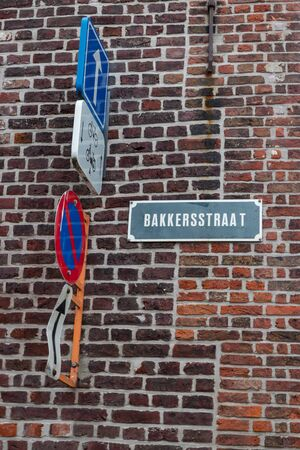Bakkersstraat Sign on Brick Wall with Traffic Signs in Bruges Belgium