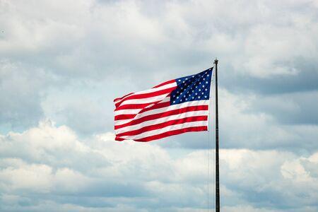 American Flag on Flagpole Against Cloudy Bluish Sky
