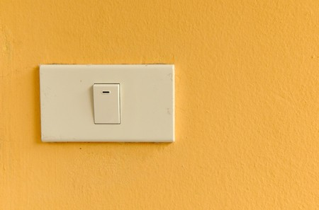 The white switch on orange wall Stock Photo - 7347165