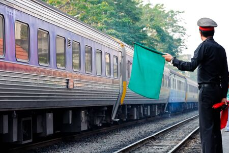 Green flag signal from station master,Thailand Stock Photo