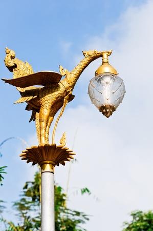 Golden bird statue on the top of pole in active ground,Kanchanaburi Thailand photo