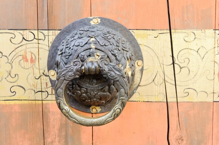 Old dragon knocker on the red wooden door of Chinese temple photo