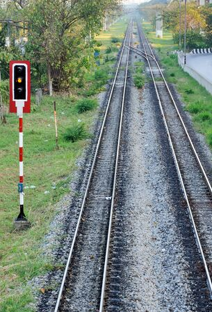 railroad crossing: Yellow light of signal pole shows for the train leaving the station