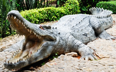 Statue large crocodile in front of crocodile ponds inside the zoo photo