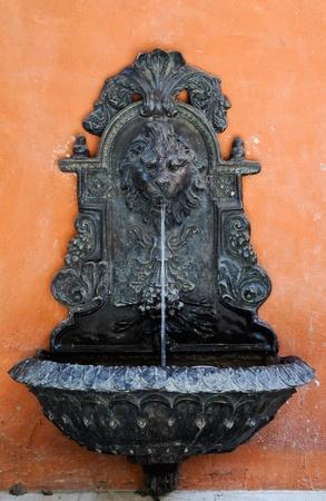 European style of lion fountain on the orange wall photo