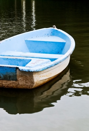 Lonely row boat on the tranquil lake in the evening. photo