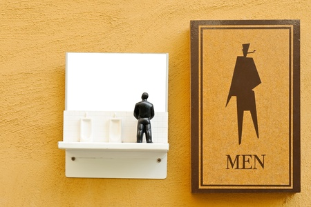 Lovely symbol of male toilet on the orange wall. photo