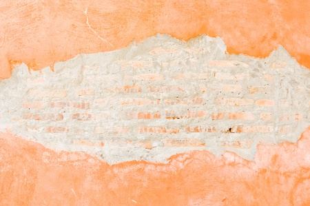 Orange brick walls which cracked until see the brick inside. photo